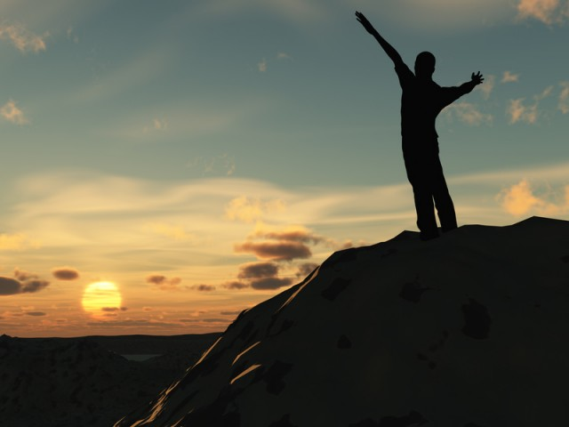 Meeting of the sun. The man on high mountain with the hands lifted above, on a background of a sunset