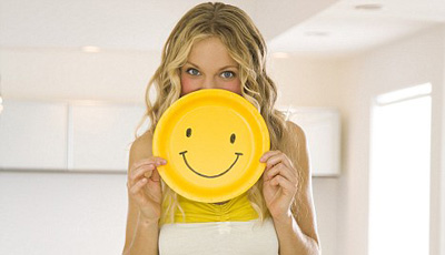 Young Woman Holding Smiley Face --- Image by © RCWW, Inc. /RCWW, Inc./Corbis
