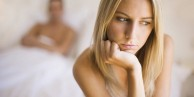 MODEL RELEASED. Relationship trouble. Woman sitting with her back to her partner.