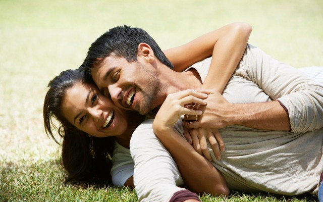 South American couple laying in grass