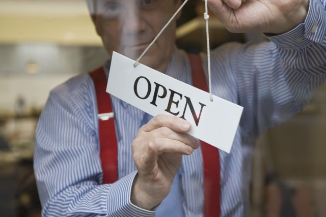 Man hanging open sign on door/thinkstock photo